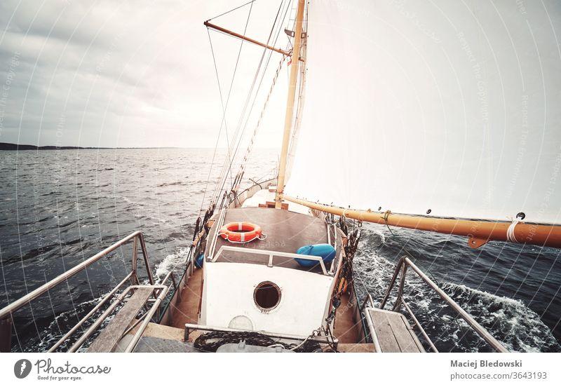 Segeln gegen die Sonne, farbig getöntes Bild eines alten Schoners. Boot Abenteuer Urlaub Mast Wasser MEER Meer Freiheit Schiffsdeck retro altehrwürdig