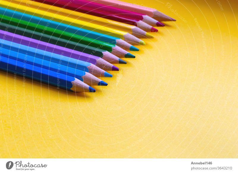 Farbstifte in Regenbogenfarben in einer Reihe auf orangefarbenem Hintergrund, retro-moderner Gestaltungsraum für Text Zeichnung Schule farbenfroh Bildung weiß