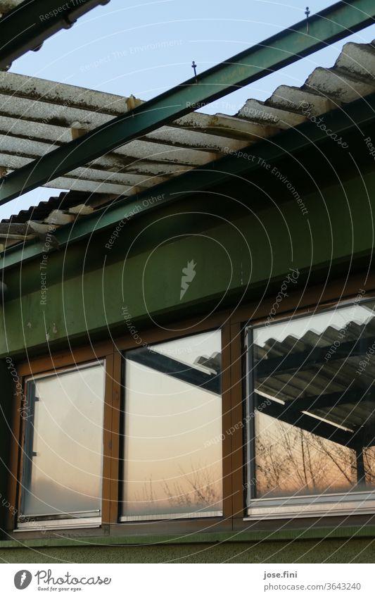 Heruntergekommenes, nur teilweise erhaltenes Welldach,  über Fenstern in denen sich der Sonnenuntergang spiegelt. Gebäude verfallen welldach Vergänglichkeit