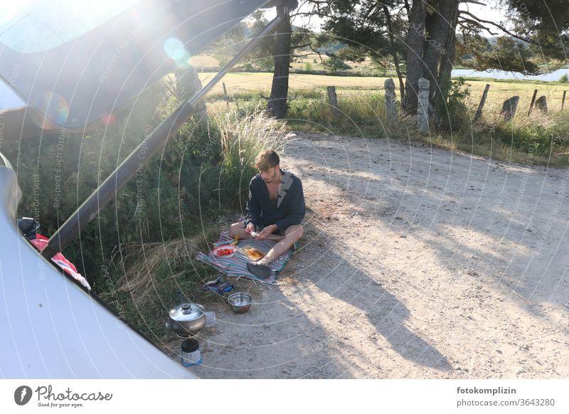 junger Mann sitzt auf einem Feldweg und bereitet eine Picknickpause vor on the road again Ferien & Urlaub & Reisen unterwegs Weg Freiheit Freizeit & Hobby