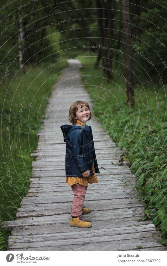 Mädchen mit Regenjacke freut sich, stehend auf einem Holzsteg in einem Wald Kleinkind süß stylisch gelb Knöterichgewächs Birkenwald Naturschutzgebiet Rhön