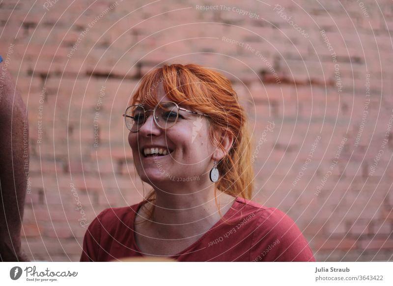 Lachende Frau mit Rostroten Haaren und stylischer Brille sitzt vor Backsteinmauer lachen Austrahlung kupfer Kupferfarben Brillenträger schön rosa orange