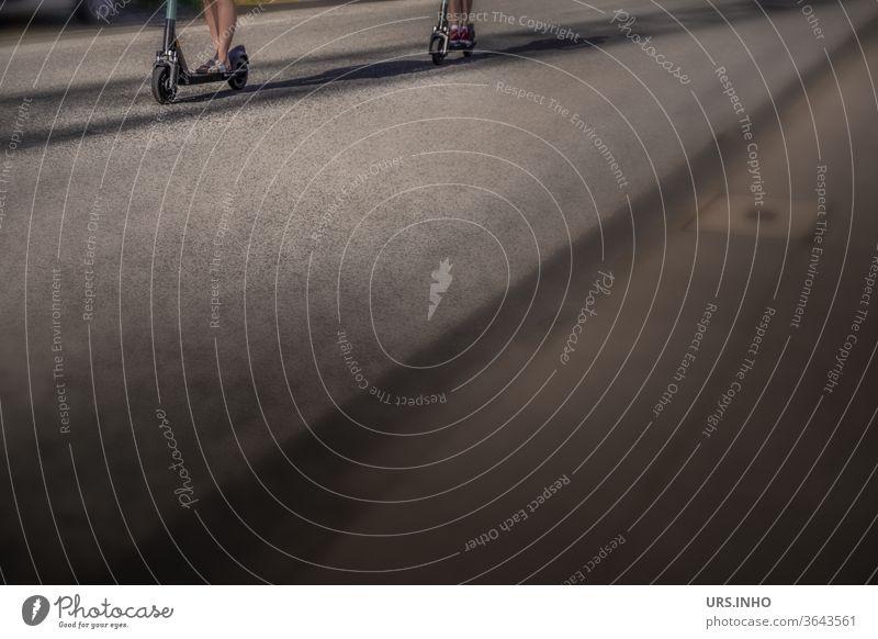 es sind nur die Beine von zwei Frauen, die auf dem heißen Asphalt der Straße mit dem  Cityroller unterwegs sind, zu sehen | Detailansicht mit viel Textfreiraum