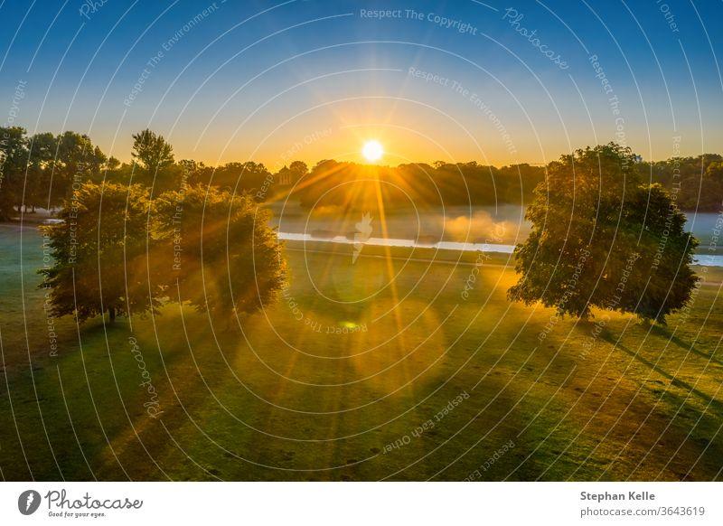 Sonniger Morgen im Park, Luftaufnahmen im Englischen Garten von München, Sonnenstrahlen scheinen durch eine Baumgruppe Natur neblig Wiese grün Sitzung Punkt