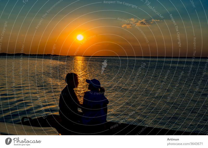 Silhouette eines verliebten Glückspaares, das bei Sonnenuntergang am Strand mit orangefarbenem und blauem Himmel sitzt und sich küsst. Sommerurlaub und Reisekonzept. Romantisches junges Paar, das sich am Meer trifft.