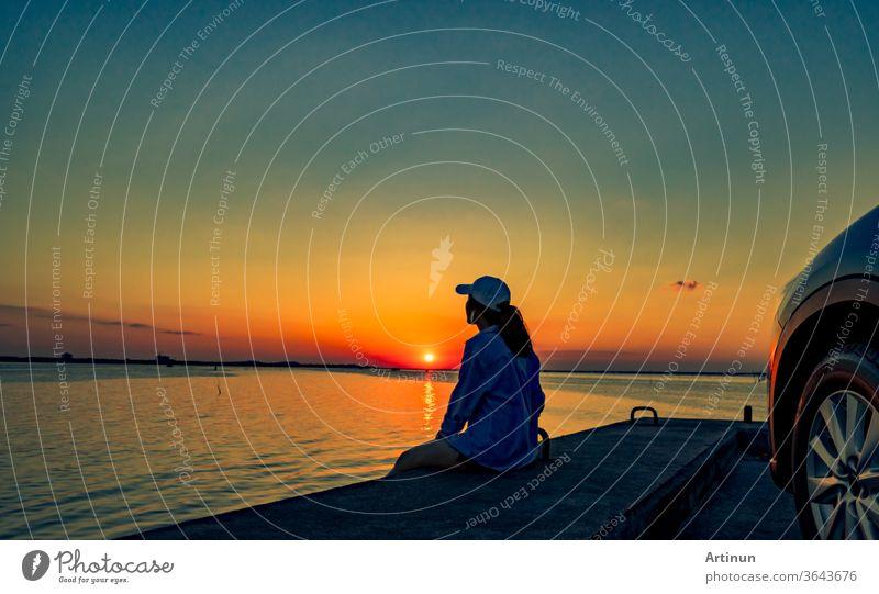 Einsame junge Frau trägt eine Mütze, die sich bei Sonnenuntergang allein vor dem Auto mit orangefarbenem und blauem Himmel am Strand entspannt. Sommerurlaub und Reisekonzept.