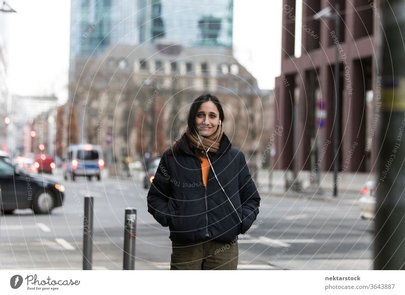 Attraktive junge indische Frau posiert an Straßenecke Junge Frau Ethnie der Indianer Musik Kopfhörer mittlere Aufnahme Hörbuch hören Fokus auf den Vordergrund