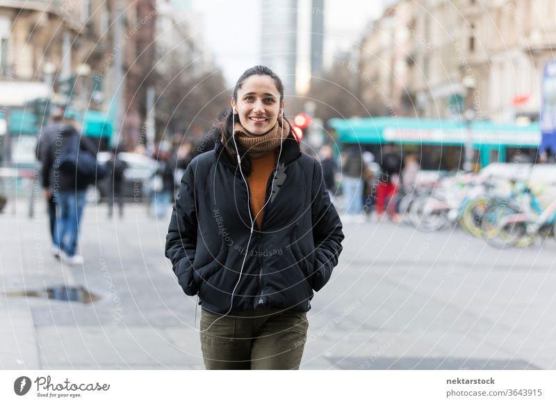 Junge indische Frau geht auf der Straße, hört Kopfhörer und lächelt in die Kamera. Junge Frau Ethnie der Indianer Musik mittlere Aufnahme Hörbuch hören