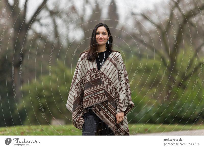 Junge Frau mit gebräunter Hautfarbe, die im Park einen Poncho trägt und lächelt. Ethnie der Indianer nahöstliche Ethnie Kopfhörer mittlere Aufnahme Hörbuch