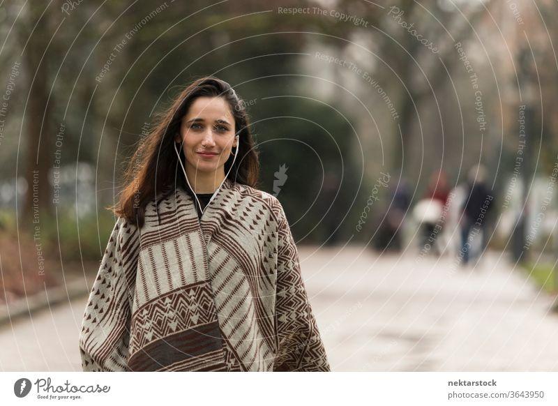 Junge indische Frau mit Poncho und Kopfhörern, die im Freien für die Kamera lächelt. Mittlere Aufnahme. Junge Frau Ethnie der Indianer nahöstliche Ethnie