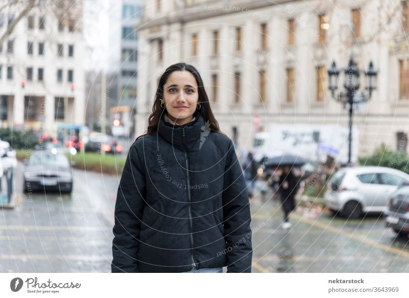 Junge indische Stadtbewohnerin, die in der Stadt posiert und in die Kamera schaut. Junge Frau Ethnie der Indianer mittlere Aufnahme Fokus auf den Vordergrund