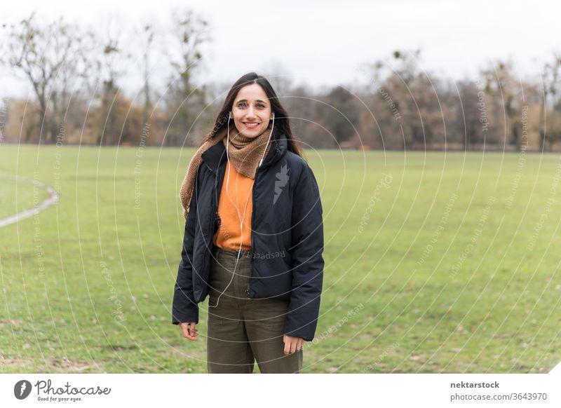 Junge indische Frau lächelt auf dem Rasen eines öffentlichen Parks. Vorderansicht. Junge Frau Ethnie der Indianer Musik Kopfhörer mittlere Aufnahme Hörbuch