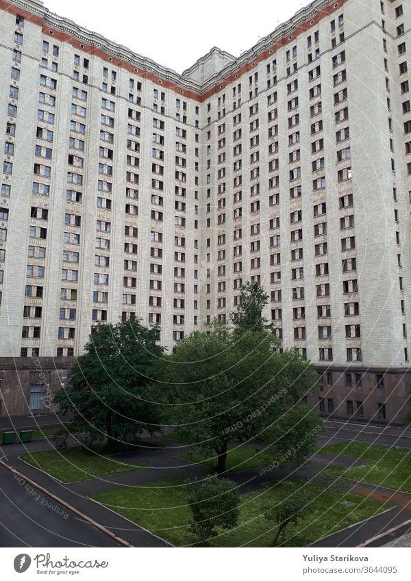 Foto eines hohen Wohnblocks mit Balkonen in Moskau. Wohnwohnungen im Hintergrund der Architektur. Gemeinsames Hausobjekt mit grauen Wänden und Fenstern. Wohnheim der Moskauer Staatsuniversität.