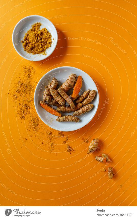 Kurkuma Wurzeln in einer Schüssel und Pulver auf einem orangen Hintergrund. Draufsicht, gesunde Ernahrung. gelb Curcuma Kräuter & Gewürze Farbfoto