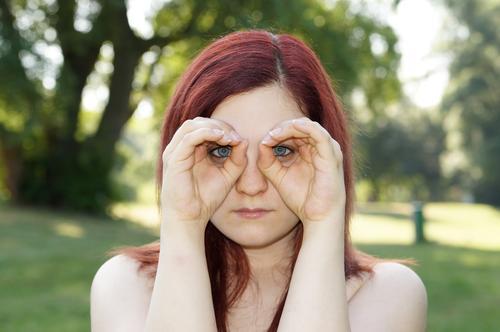 Hände, die Ferngläser imitieren beobachten Suche Blick Überwachung sehen Fernglas Brille spionieren Frau Mädchen jung im Freien Natur Porträt rote Haare Sommer