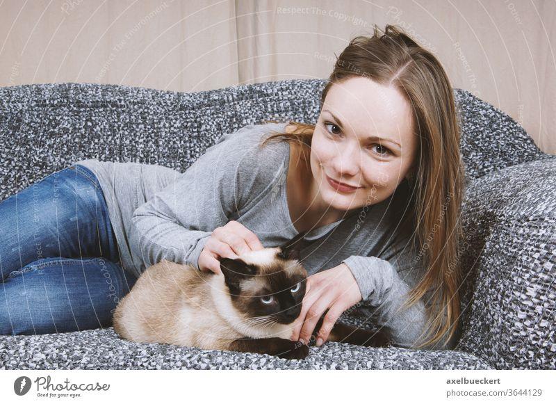 glückliche junge Frau entspannt sich mit Katze auf dem Sofa Haustier Tierliebe Kraulen Streicheln Kuscheln zuhause entspannen Mädchen Zuneigung Erwachsener