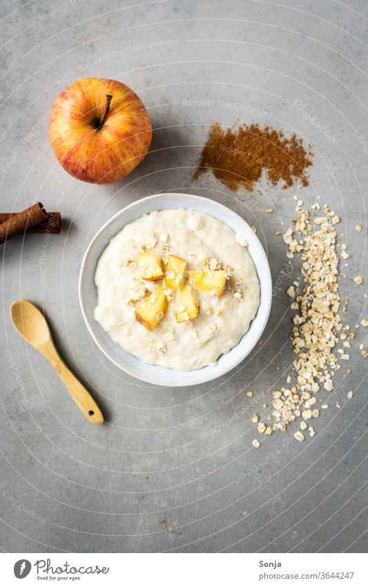 Warmer Haferbrei mit Apfel in einer weißen Schüssel. Zutaten, rustikaler Hintergrund Porridge Frühstück Haferflocken Schalen & Schüsseln Mahlzeit organisch