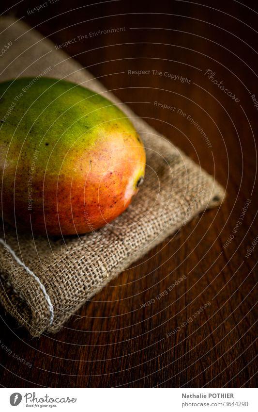 Mango auf Sackleinen Mangofrucht Farbfoto Holztisch Licht Frucht Südfrüchte juce jucy saftige Früchte Lebensmittel Gesunde Ernährung frisch