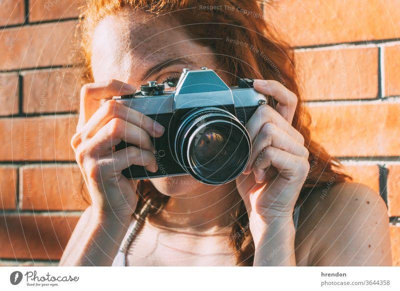 junge Frau hält eine analoge Kamera und schaut durch den Sucher veraltet Antiquität Antike Fotokamera klassisch Klassik klicken abschließen elektronisch Gerät