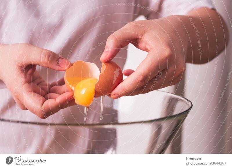 nicht erkennbare Person, die ein Ei in einer Schüssel aufschlägt gebrochen Lebensmittel Panzer backen Pause Essen zubereiten Hand Kochen Utensil hölzern Brechen