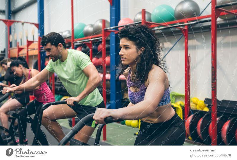 Athleten, die Indoor Airbike fahren Luftrad Frau Training Menschengruppe durchkreuzen passen Fitnessstudio Cross-Training Fahrrad Ausdauer Kraft Person jung