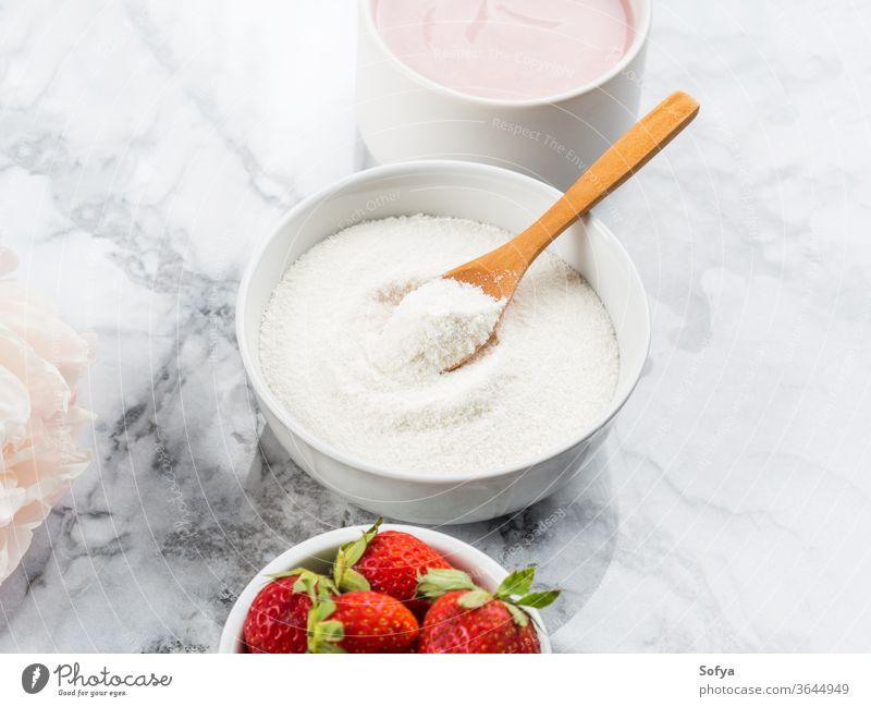 Kollagen-Proteinpulver in Schale auf Marmor Pulver Ergänzung Joghurt Lebensmittel Gesundheit Schönheit Ernährung Erdbeeren rosa Gesicht Kollagenpulver