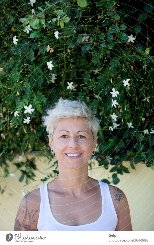 Frau mit geblümten Tattoos auf dem Arm. Mädchen jung Schönheit Behaarung schön Hintergrund Porträt blond Model Erwachsener Körper Kaukasier Lächeln Lifestyle