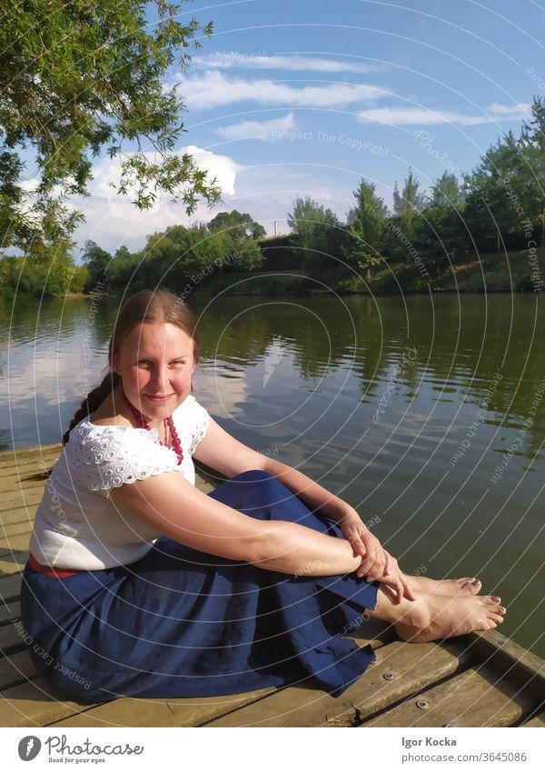 Porträt einer lächelnden Frau, die auf dem Pier über dem See sitzt Teich Lächeln Sitzen Sonnenlicht Seitenansicht Blick in die Kamera Erwachsener reif Bäume