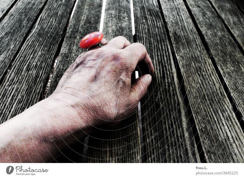 Obwohl mit schickem roten Ring geschmückt, wartet die alte Frau im Kaffegarten vergeblich auf ihr Rendezvous. Hand Bistrotisch Café Schmuck verkrampf Holztisch