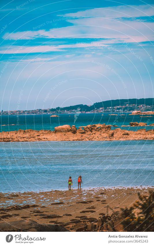 kinder am strand mit blick auf das meer in galizien (spanien) am horizont Lifestyle MEER Kindheit Spaß spielen Sonne Meer Sommer Spanien Lächeln Sand Tourismus