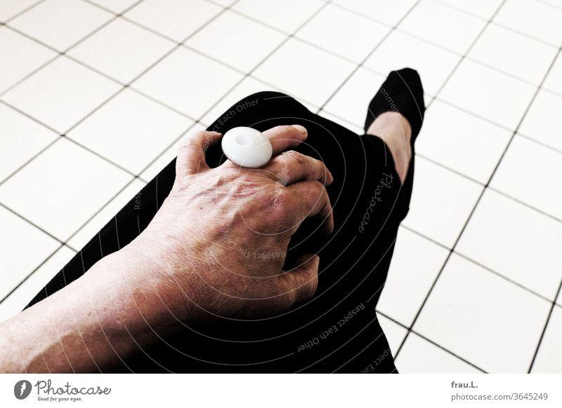 Er war nicht gekommen, jetzt saß die alte Frau allein in ihrer Küche und hatte den weißen Ring am Finger. Beine Fuß Fussboden Kacheln Fliesen Hand Schmuck