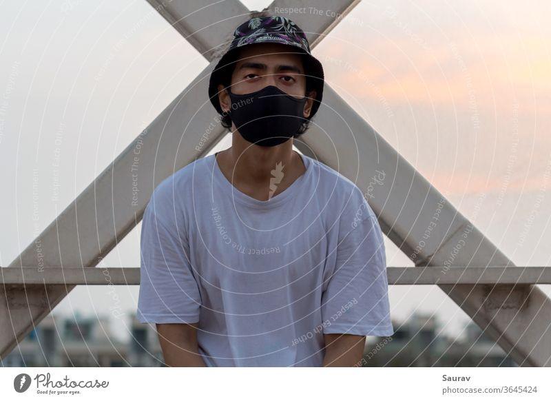 Ein junger Mann setzte eine schützende Gesichtsmaske auf, um eine Infektion mit dem Coronavirus in einer Stadt zu vermeiden, während er eine blumige Eimermütze und ein weißes T-Shirt trug.
