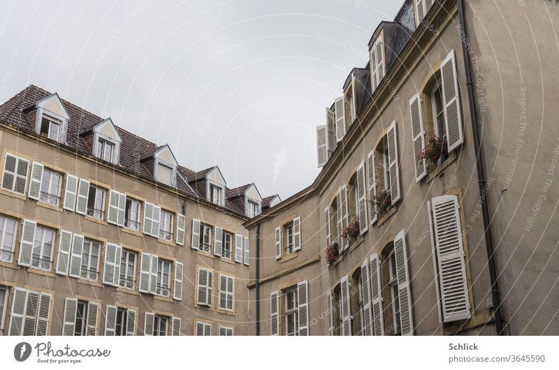 Häuserfront in Metz Lothringen Fassaden Front Frankreich Fenster Dachgauben Klappläden Himmel grau bedeckt Winkel alt