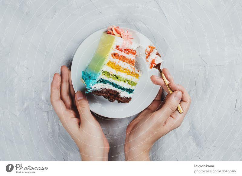 Flachgelegtes Regenbogen-Veganer-Kuchenstück in Frauenhänden auf grauem Hintergrund Diät Geschenk rosa Snack geschmackvoll Glück Mädchen Gebäck Hand Geburtstag