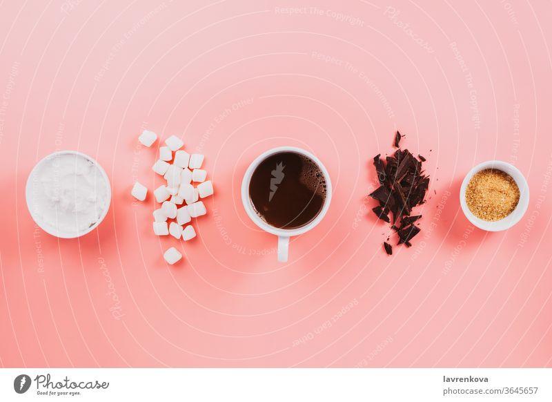 Flatlay aus veganem Kakao, Schokolade, Kokosnusscreme, Zucker und vegetarischen Marshmallows auf rosa fallen Winter Herbst Bestandteil legen flach gemütlich