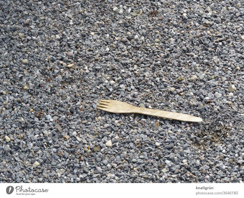 Bio Einwegbesteck Gabel aus Holz liegt auf Straßenschotter Bioprodukte ökologisch Umwelt Umweltbewusstsein nachhaltig Ernährung natürlich Außenaufnahme Farbfoto