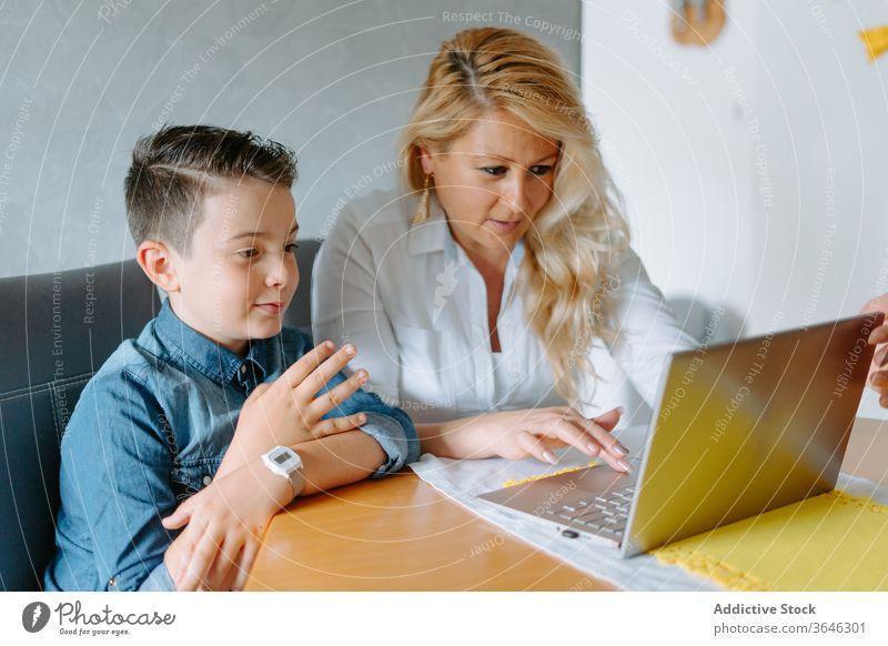 Positive Mutter mit Sohn am Laptop modern heimwärts Schulbildung Inhalt Browsen benutzend Wohnzimmer Eltern Tutorin lernen Lehrer Lektion Tisch Netbook