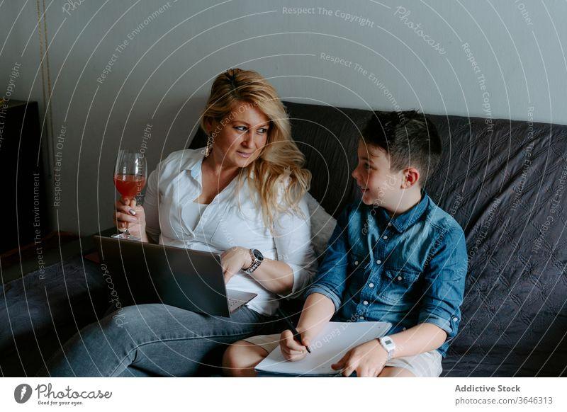 Positive Mutter und Sohn ruhen mit Laptop auf dem Sofa benutzend modern Inhalt Glück Lächeln Glas heiter lernen Schot Cocktail sich[Akk] entspannen Papier