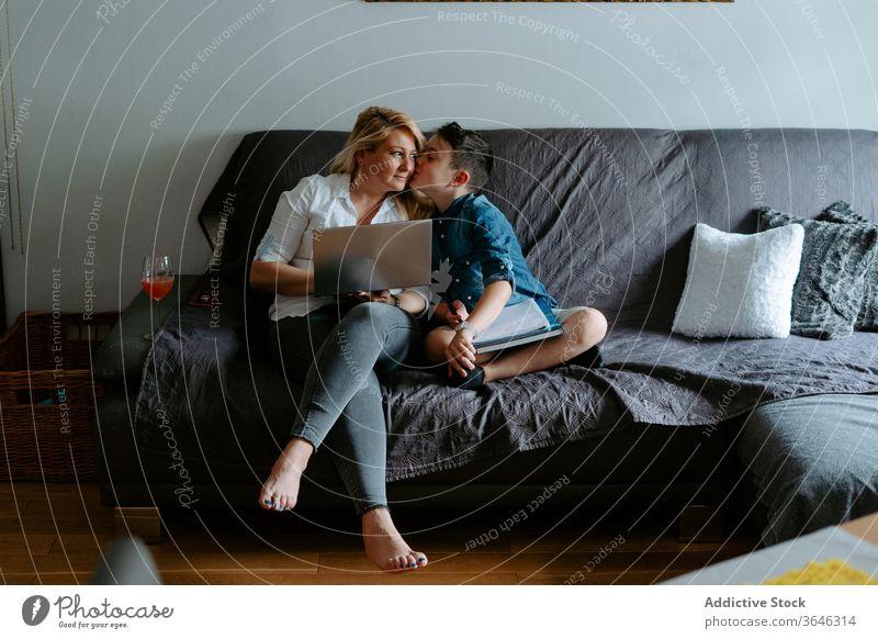 Positive Mutter und Sohn ruhen mit Laptop auf dem Sofa benutzend Kuss modern Inhalt Glück Lächeln Glas heiter lernen Schot Cocktail sich[Akk] entspannen Papier