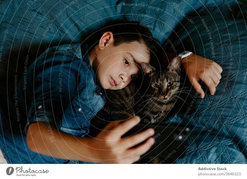 Kleiner Junge und Katze nehmen sich mit dem Handy auf dem Bett selbst auf Smartphone niedlich lässig Foto Selfie Zusammensein Umarmung Komfort süß