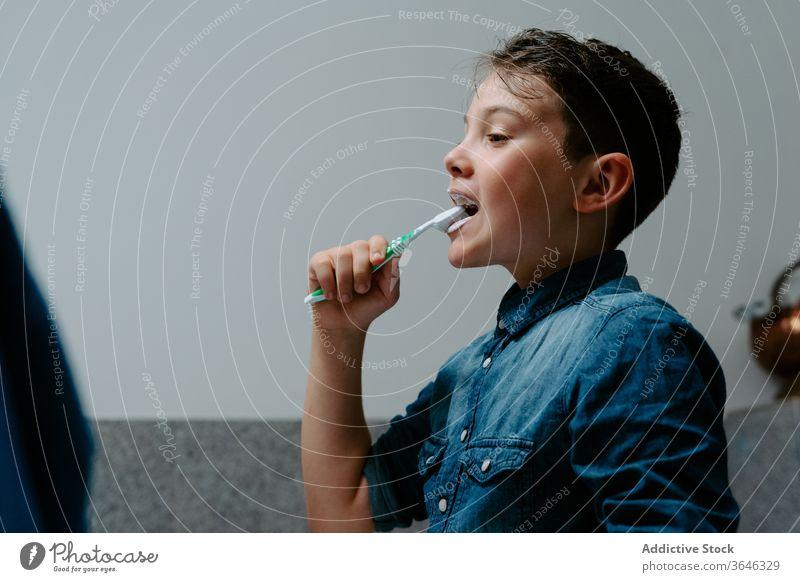 Süßer Junge beim Zähneputzen im gemütlichen Badezimmer Bürste Zahnbürste Morgen Hygiene bezaubernd positiv Routine dental Sauberkeit Hemd Jeansstoff Kunststoff