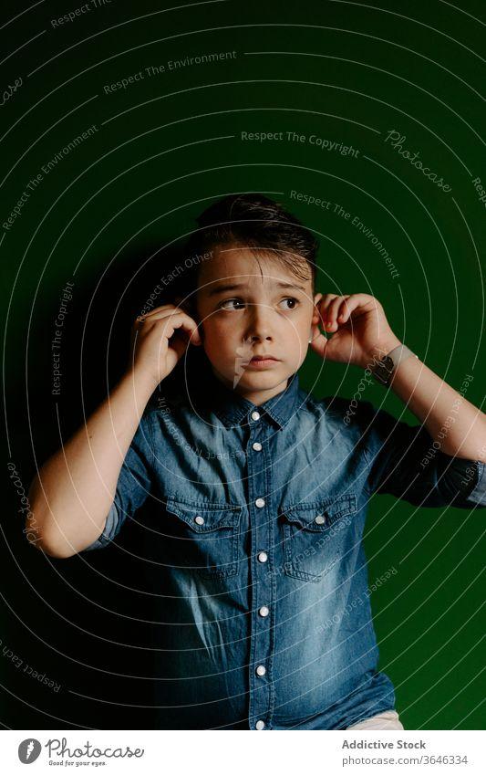 Schuljunge schaut weg und posiert mit Ohrstöpseln in bunter Wand Junge selbstbewusst cool erreichen emotionslos freundlich Stil Lifestyle Kind Porträt zeigen