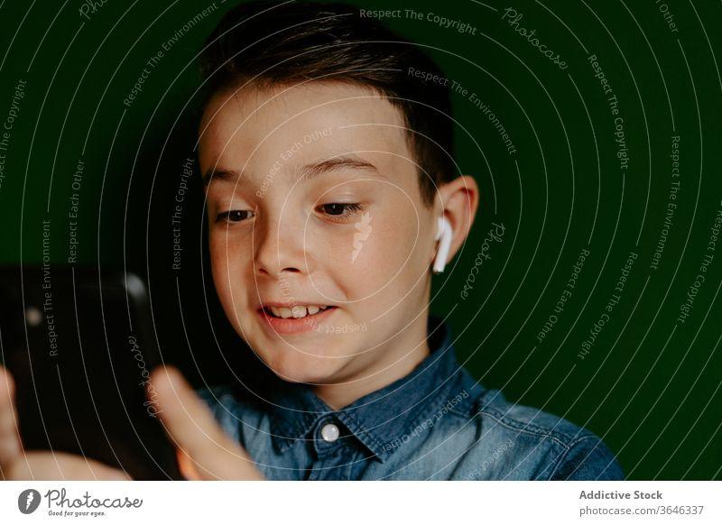 Zufriedener Junge in Ohrstöpseln mit Smartphone benutzend zuhören Musik Inhalt positiv Apparatur Drahtlos modern Favorit Mobile Telefon Surfen soziale Netzwerke