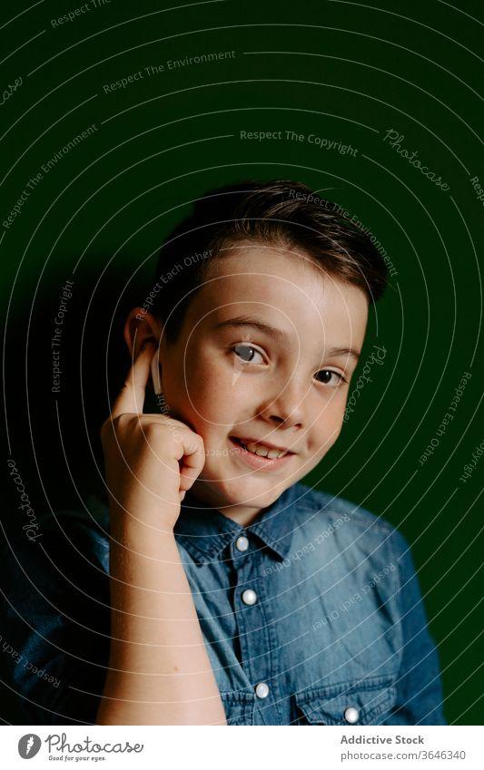 Schuljunge schaut weg und posiert mit Ohrstöpseln in bunter Wand Junge selbstbewusst cool erreichen freundlich Stil Lifestyle Kind Porträt Lächeln Optimist