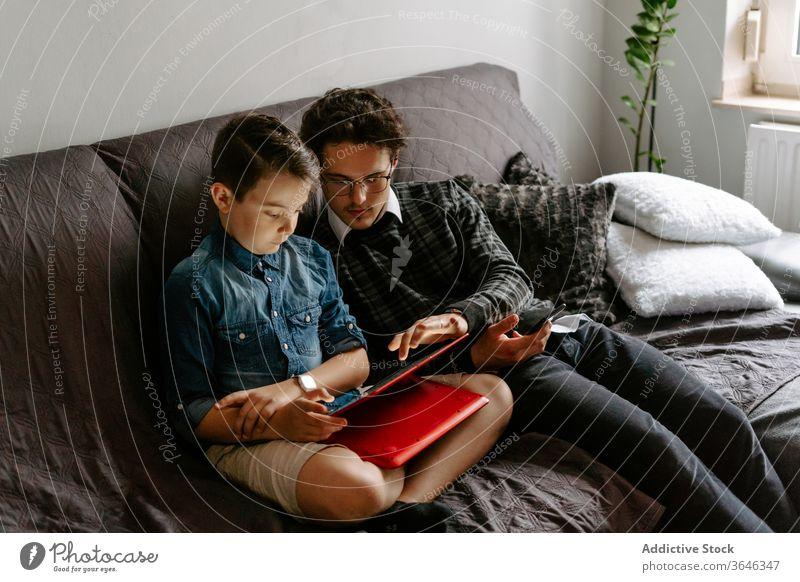 Schuljunge mit Bruder blättert auf einem bequemen Sofa Geschwister Junge Tablette benutzend Apparatur Zeitgenosse sich[Akk] entspannen ruhen Browsen Talkrunde