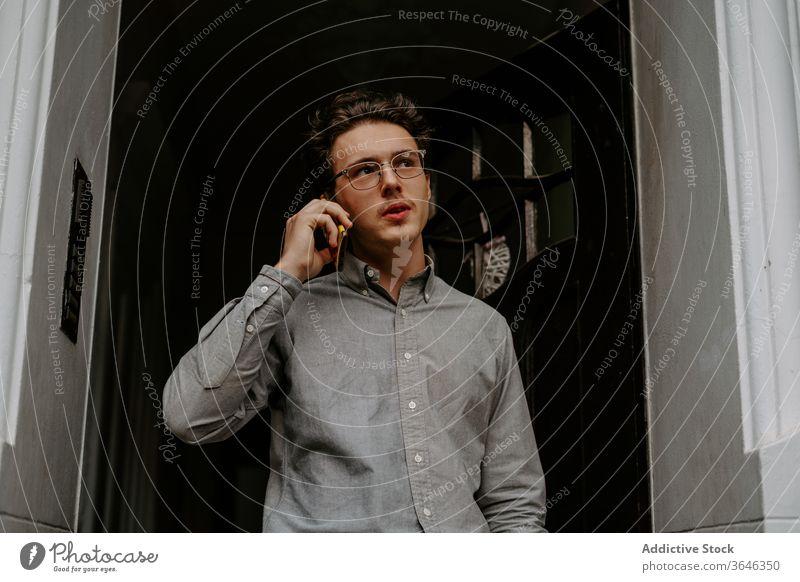 Fokussierter junger Mann spricht auf Smartphone Telefonanruf reden Gespräch Konzentration besinnlich Gang Kommunizieren Gerät Brille Hemd Apparatur Anschluss