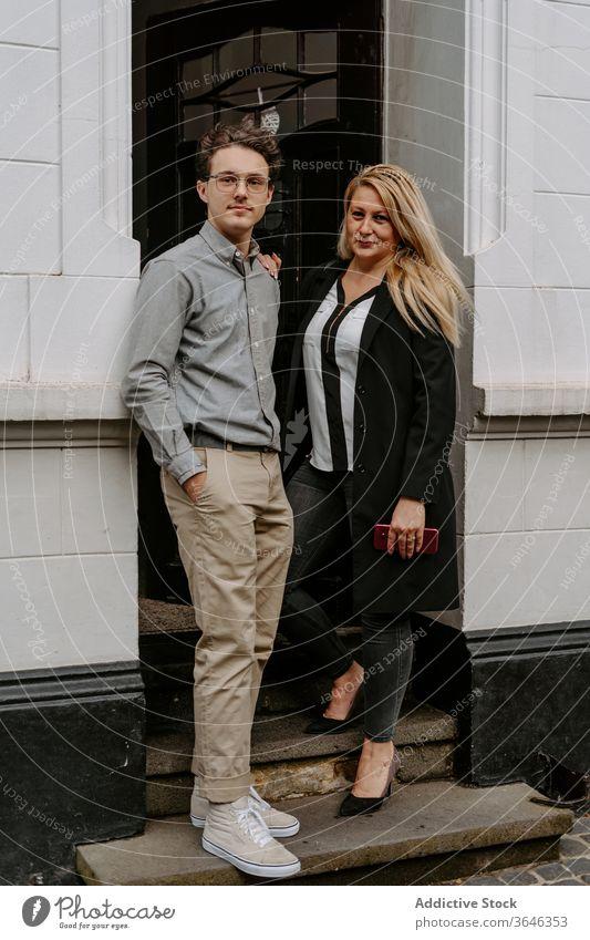 Zufriedenes Ehepaar im Eingang auf der Straße Paar Kollege formal modern Gebäude positiv Inhalt selbstbewusst professionell Hand-in-Tasche Business Pause Outfit