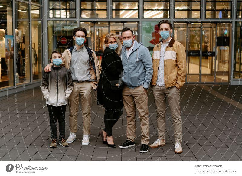 Positive Freunde in Gesichtsmasken gegen Glasgebäude relativ Mundschutz Atemschutzgerät Inhalt positiv Gebäude Tür modern Hand-in-Tasche Stil Coronavirus
