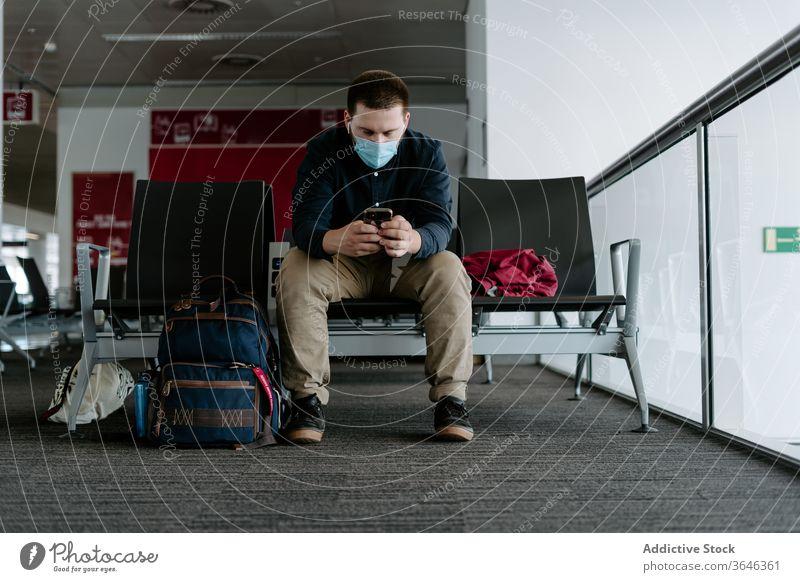 Männlicher Passagier in Atemschutzgerät mit Smartphone beim Warten auf den Flug Mann Browsen Mundschutz Flughafen Coronavirus Gerät warten reisen Seuche