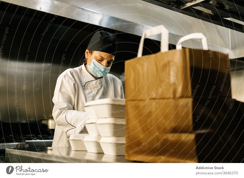 Fokussierte Köchin mit Atemschutzmaske packt Essen zum Mitnehmen Frau Küchenchef Atemschutzgerät Rudel Imbissbude Konzentration Tüte Restaurant Coronavirus